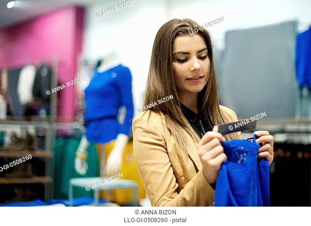 Beautiful woman checking tag in a boutique Debica, Poland