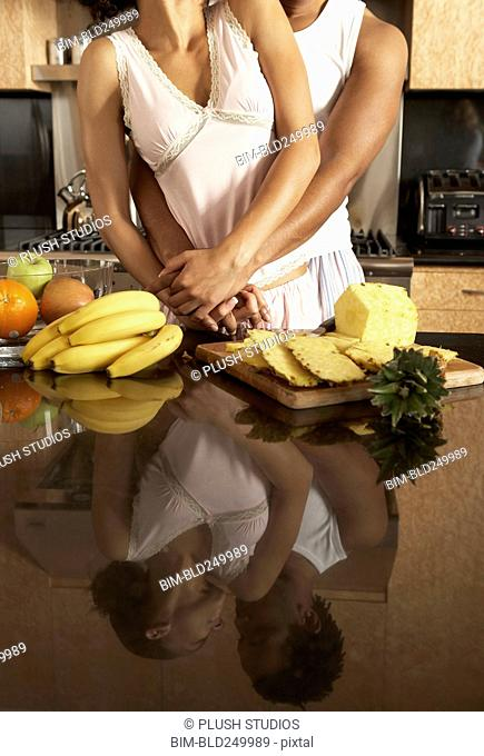 Reflection on counter of couple hugging in domestic kitchen