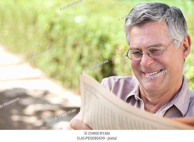 Smiling senior man reading newspaper outdoors