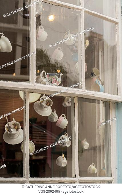 quirky tea cups suspended in vintage, indie tea shop window in Monmouth, Wales, Uk