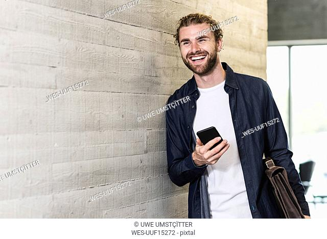 Happy casual businessman standing on office floor holding cell phone and briefcase