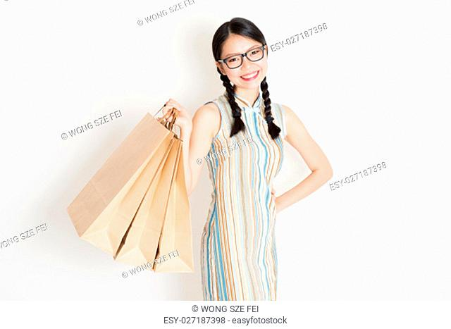 Portrait of young Asian girl in traditional qipao dress shopping, hand holding paper bag, celebrating Chinese Lunar New Year or spring festival
