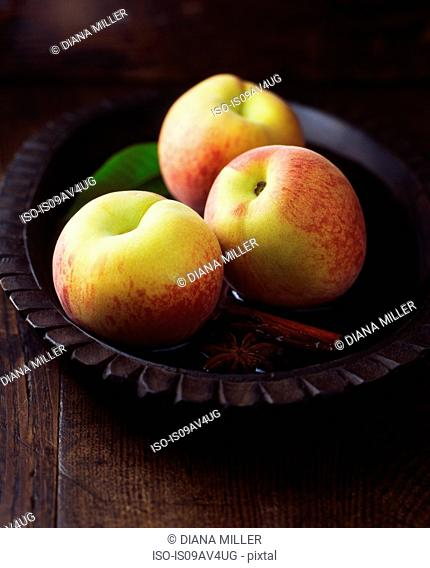 Peaches and leaves with cinnamon stick and star anise in vintage wooden bowl of water