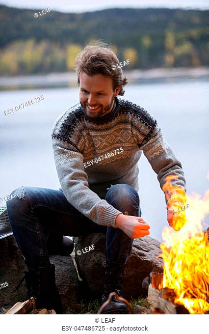 Smiling young man warming hands by bonfire on lakeside camping