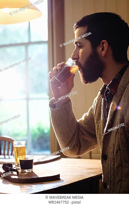Profile view of hipster man drinking a shot
