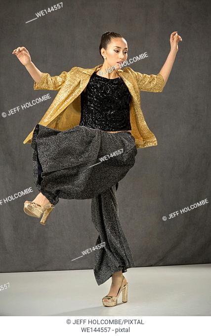 Young woman dancing, wearing gold jacket, baggy black pants, and black top in full length fashion shoot