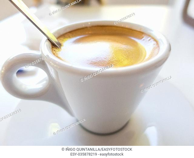 macro of white small cup with espresso coffee, with metal spoon, on table of restaurant bar or cafe