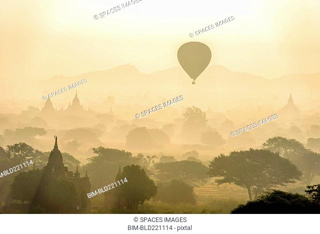 Aerial view of hot air balloons flying over towers