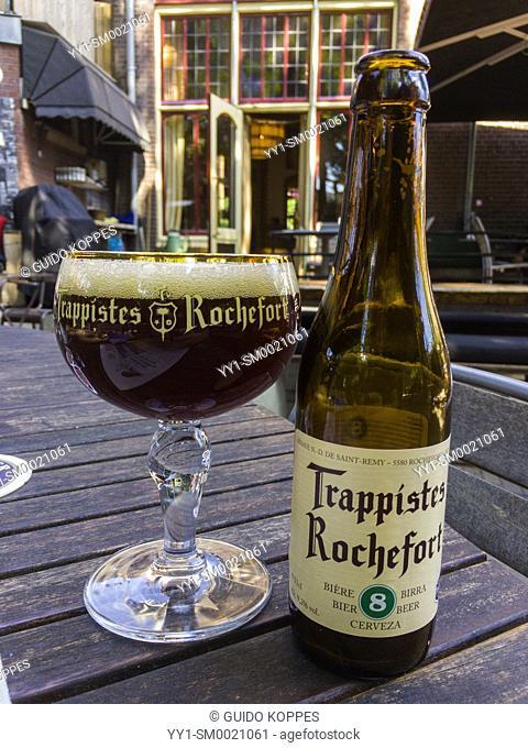 Tilburg, Netherlands. Freshly poured Rochefort No. 8 Beer in bottle and glass on cafe terrace table