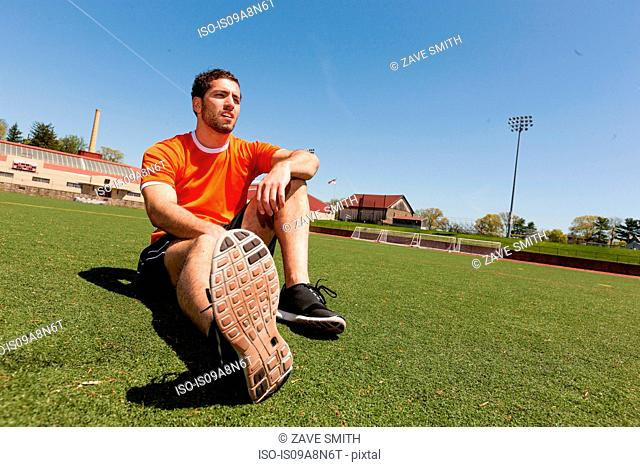 Young man taking a break on sport stadium grass