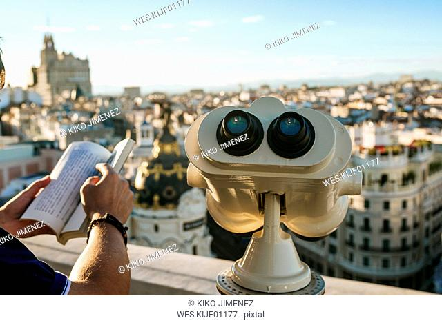 Spain, Madrid, close-up of binoculars and man holding book with cityscape in background