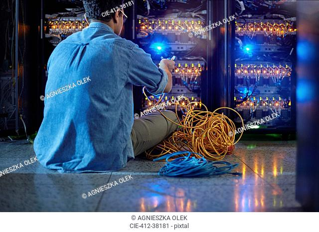 Male IT technician with cables at panel in dark server room