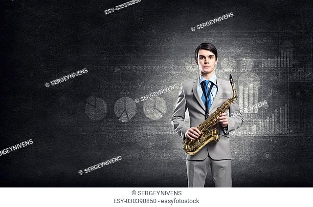 Young businessman with saxophone in hands and diagrams at background