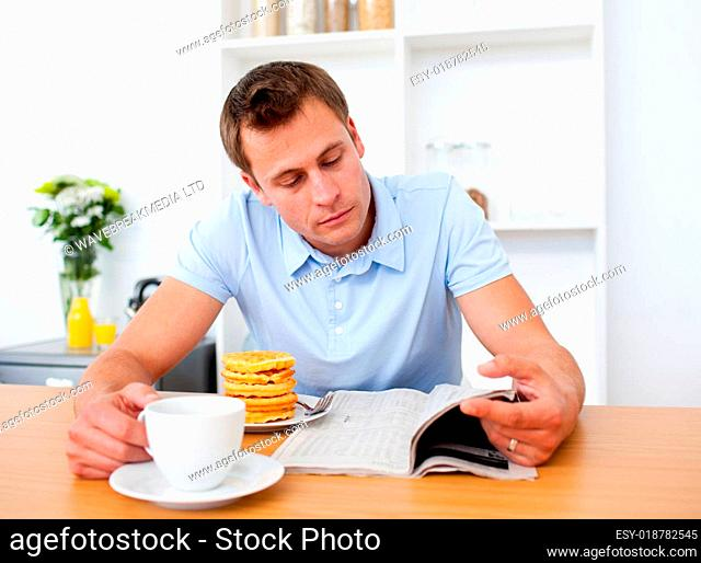 Concentrated man reading a newspaper while having breakfast