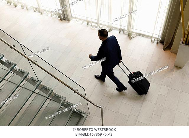 High angle view of Hispanic businessman rolling luggage in hotel lobby