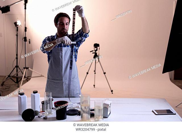 Male photographer checking camera filmstrip