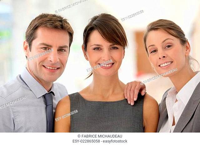 Cheerful business team standing in hallway