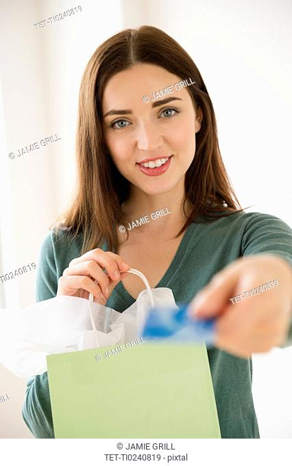 Young woman holding shopping bag and credit card