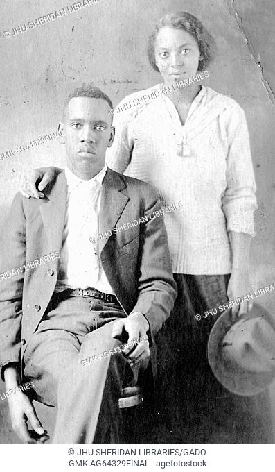 Young african-american couple, the man sitting in a chair wearing a suit, with a blank facial expression, the woman standing behind him with her hand on...