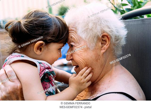 Grandmother face to face with her granddaughter on terrace