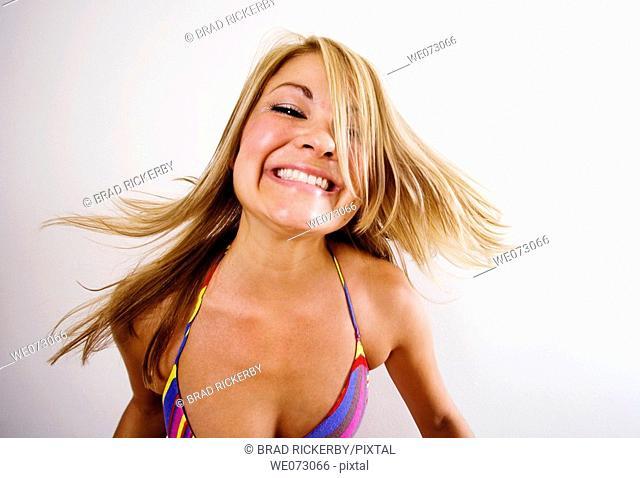 Mid 20's caucasian woman makes crazy happy face in studio portrait
