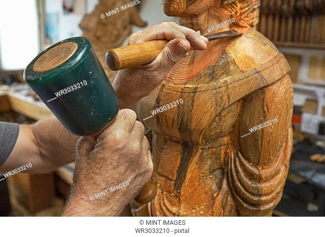 A wood carver standing in his workshop, using hand tools, mallet and chisel to shape and create decoration on a work in progress
