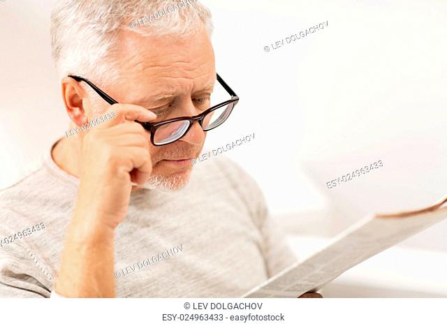 leisure, information, people, vision and mass media concept - close up of senior man in glasses reading newspaper at home