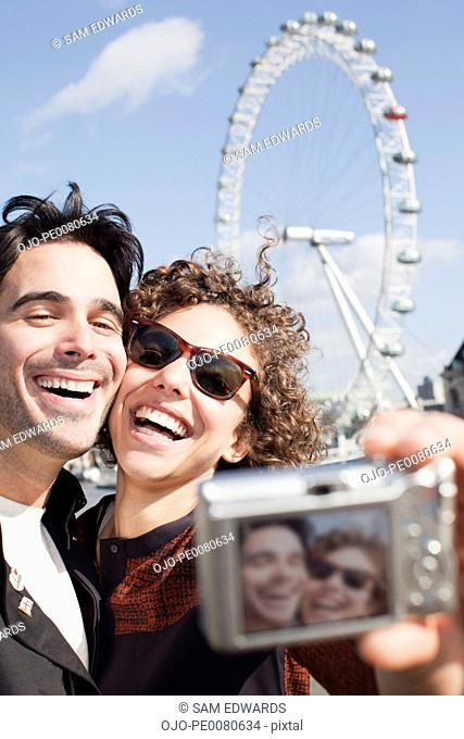 Happy couple taking self-portrait with digital camera in front of ferris wheel
