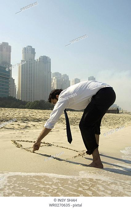 Businessman draws a house on the sand, towers in the background