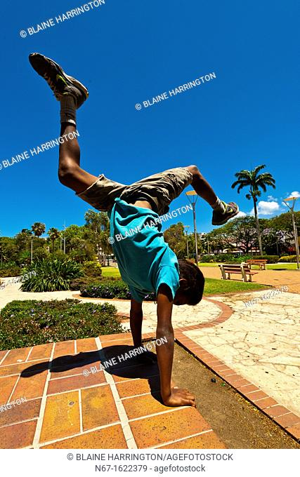 A Melanesian boy doing a handstand, Place des Cocotiers, Noumea, New Caledonia