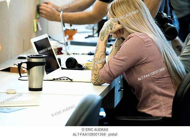 Woman concentrating on work in shared office space