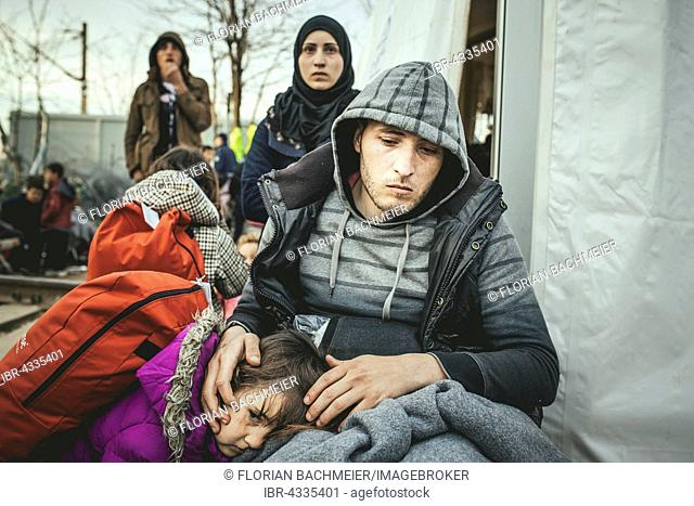 Idomeni refugee camp on the Greece Macedonia border, refugees waiting at a checkpoint, a disabled man with his family, who has been rejected from Macedonia
