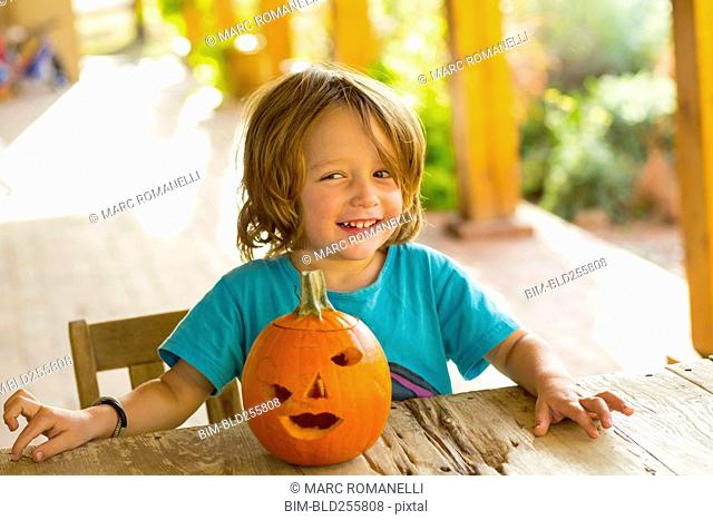 Portrait of smiling Caucasian boy with carved pumpkin
