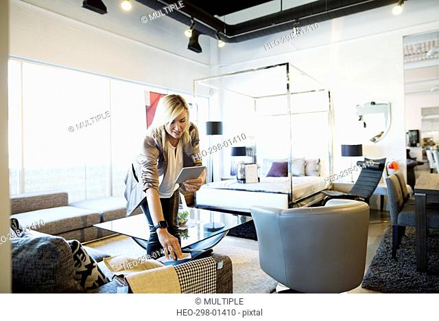 Interior designer with digital tablet browsing fabric swatches in home furnishings store