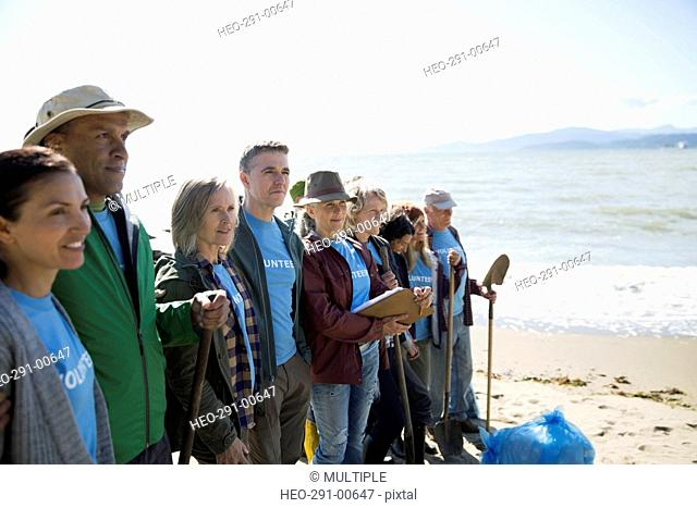 Beach cleanup volunteers standing in a row on beach