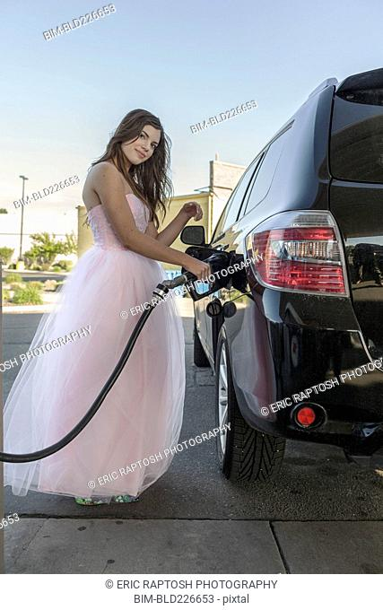 Caucasian girl wearing prom dress fueling car