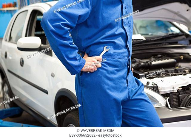 Mechanic with spanner by car
