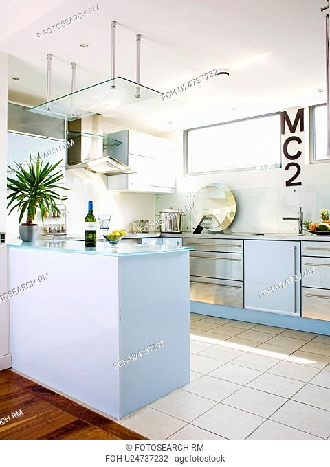 Cream ceramic floor tiles in modern white kitchen with pastel blue fitted units