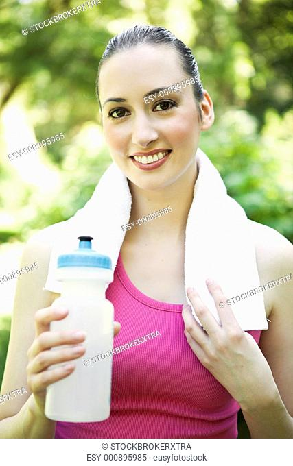A beautiful caucasian woman doing exercise holding water bottle in a park