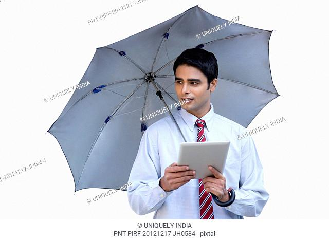 Businessman holding an umbrella and using a digital tablet