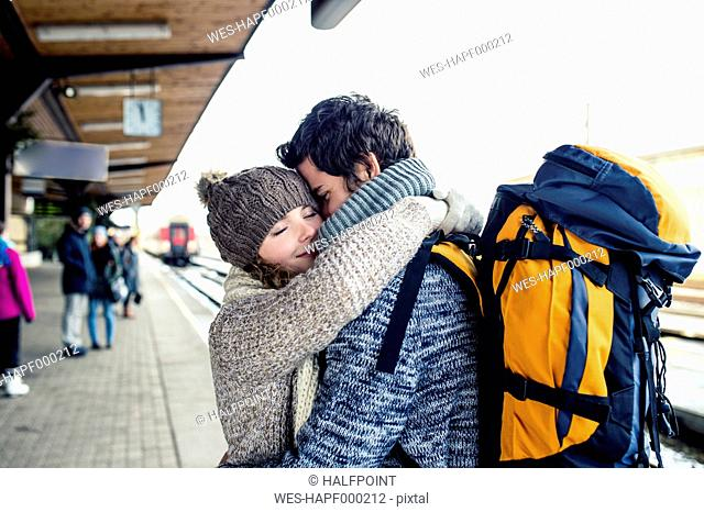 Smiling young couple embracing on station platform