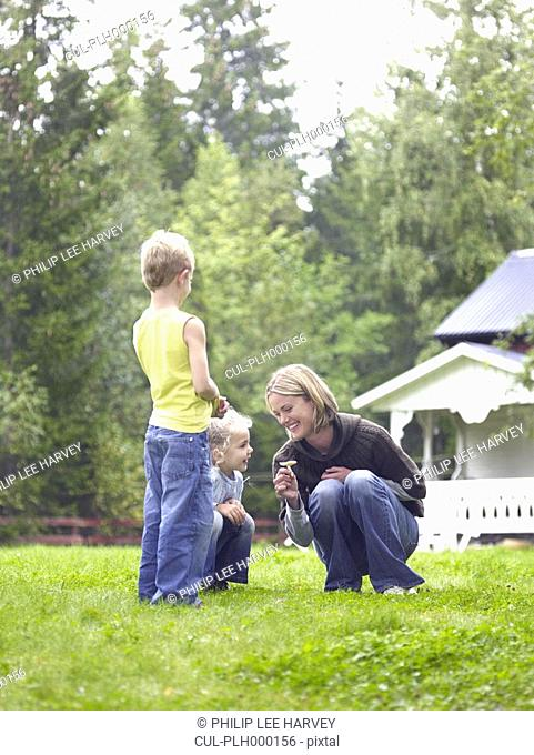 Woman with young girl and young boy in yard picking flower smiling