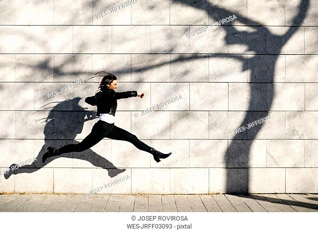 Young woman making a big jump on a wall with a shadow of a tree