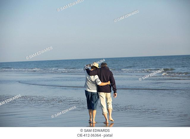 Affectionate mature couple hugging, walking in sunny ocean beach surf