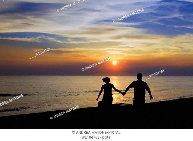 Romantic couple walking holding hands at sunset