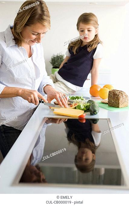 Mother preparing sandwich for daughter