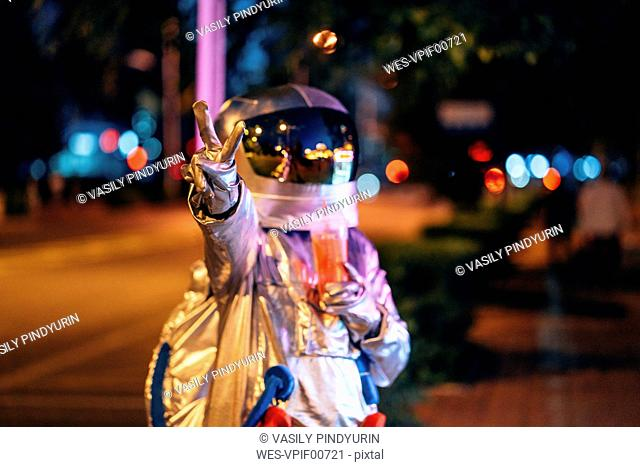 Spaceman in the city at night with takeaway drink making victory gesture
