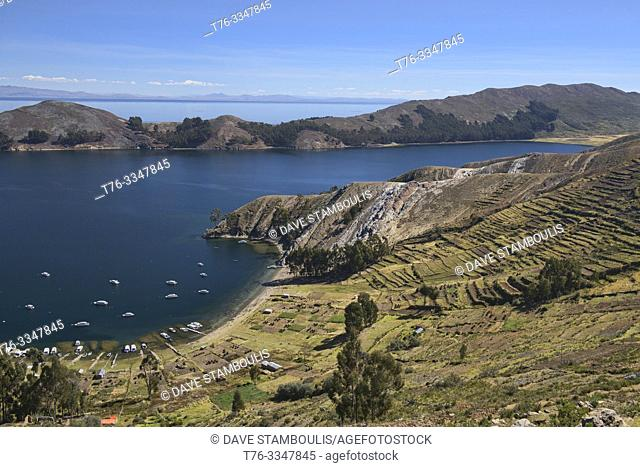 Boats in the bay and agricultural terracing on Isla del Sol, Lake Titicaca, Bolivia