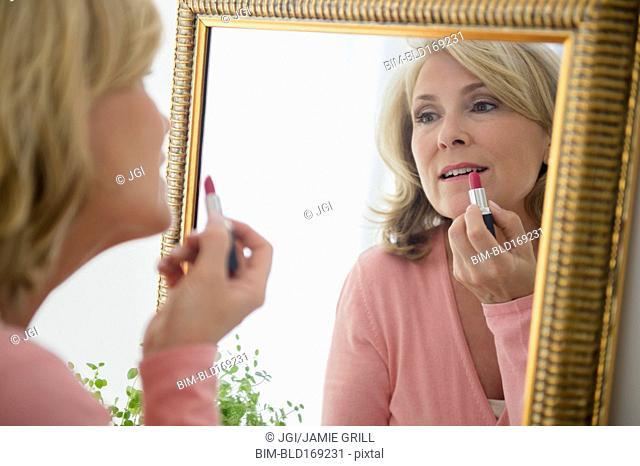 Caucasian woman applying lipstick in mirror