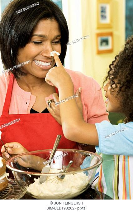 African American daughter putting icing on mother's nose